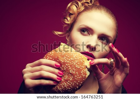 Unhealthy eating. Junk food concept. Portrait of fashionable young woman holding burger and posing over purple background. Close up. Copy-space. Perfect hair, skin, make-up and manicure. Studio shot - stock photo