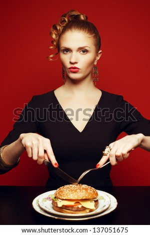 Unhealthy eating. Junk food concept. Portrait of fashionable young woman holding fork and knife and going to eat burger. Perfect hair, skin, make-up and manicure. Studio shot - stock photo