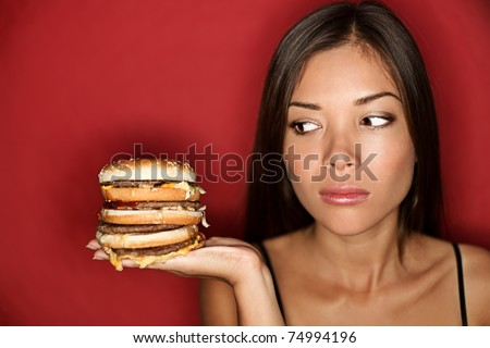 Unhealthy eating - junk food concept. Woman looking at big oversized burger thinking. Pretty Caucasian Asian model over red background. - stock photo