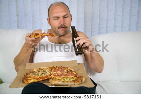 Unhealthy fat man sitting on couch drinking beer and eating pizza