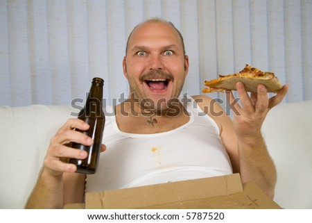 Unhealthy fat man sitting on the couch drinking beer and eating pizza - stock photo