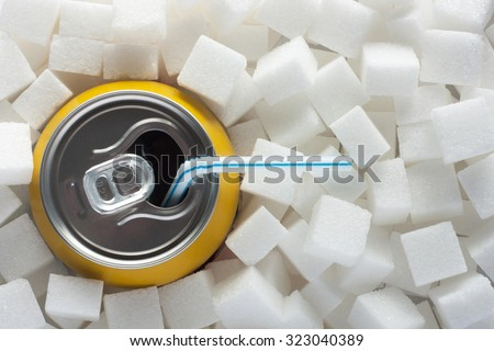 Unhealthy food concept - sugar in carbonated drink. Sugar cubes as background and canned drink with straw drink - stock photo