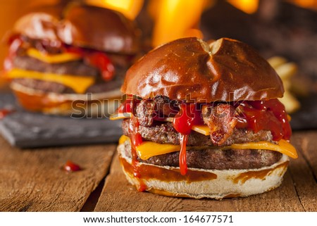Unhealthy Homemade Barbecue Bacon Cheeseburger with Fries - stock photo