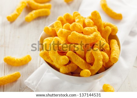 Unhealthy Orange Puffy Cheese Crisps against a background - stock photo
