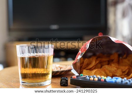 unhealthy snacks on table with skull dice and tv in background - stock photo - stock photo