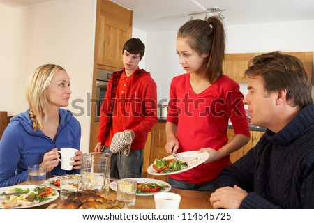 Unhelpful Teenage Clearing Up After Family Meal In Kitchen - stock photo