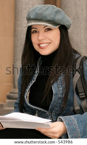 Uni student holding papers and smiling.
