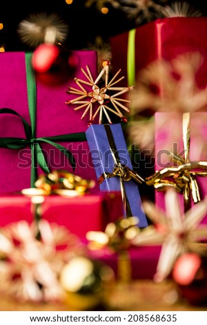 Unicolored Christmas gifts with bow knots. Shallow depth of field. Focus is on the golden bow around the blue box. Blurred shapes of baubles and straw stars in front and back.