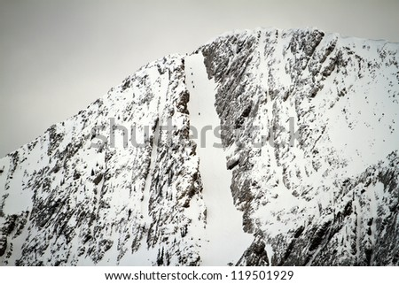 Unidentifiable Hikers in a Snowy Chute - stock photo