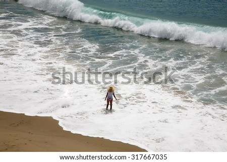 Unidentifiable people frolic in the surf of the Pacific Ocean in Laguna Beach California. Laguna Beach in Southern California a world wide tourist destination. Everyone Loves the beach and the ocean - stock photo