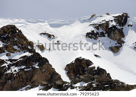 Unidentifiable skier descends a steep mountain - stock photo