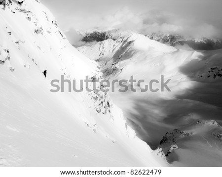 Unidentifiable skier descends a steep mountain in Alaska - stock photo