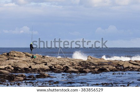 Unidentified angler or fisherman, fishing from rocky shoreline while waves crash upon the rocks.