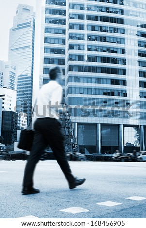 Unidentified businessman crossing the street in Singapore. There are more than 7,000 multinational corporations from US States, Japan and Europe in Singapore  - stock photo