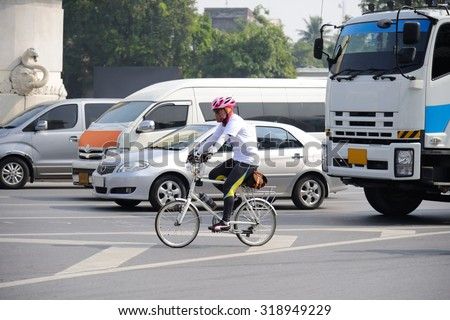 Unidentified cyclist riding his bicycle on Bangkok road