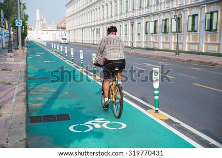 Unidentified cyclist riding on Bangkok's bike lane - stock photo