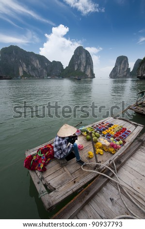 Unidentified female fruit seller sells various types of fruits on boat in Halong Bay, Vietnam - stock photo