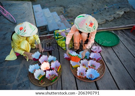 Unidentified girls sell flower lights at ancient town Hoi An - stock photo