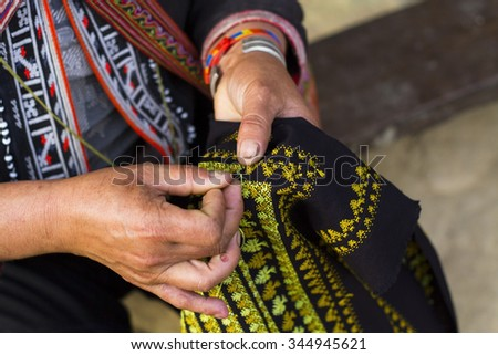 Unidentified Hmong woman's hand sewing in Sapa, Vietnam. The Hmong are an Asian ethnic group from the mountainous regions of China, Vietnam, Laos, and Thailand.