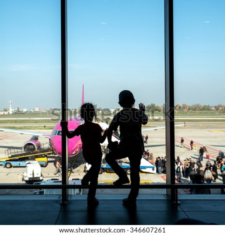 Unidentified kids looking at airplanes in the airport. The airport is named after Bologna native G. Marconi, an Italian electrical engineer and Nobel laureate. - stock photo