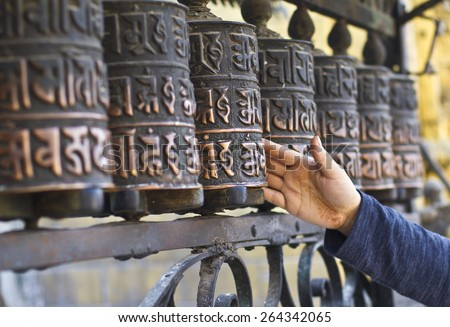 Unidentified lady spins Buddhist prayers wheels in Swayambhunath Stupa, kathmandu,Nepal - stock photo
