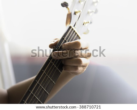 Unidentified male play guitar with left arm closeup  with sunlight guitar
