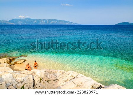 Unidentified man and woman relaxing on beautiful beach with crystal clear water on Kefalonia island, Greece - stock photo
