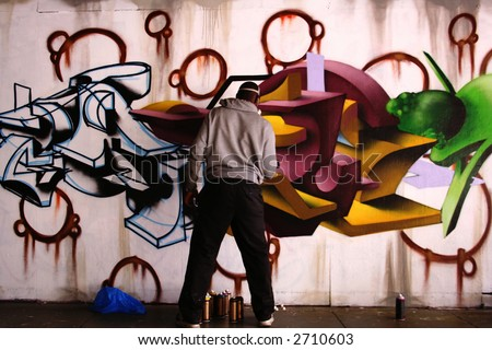 Unidentified man sprays graffiti on a wall like a vandal - stock photo