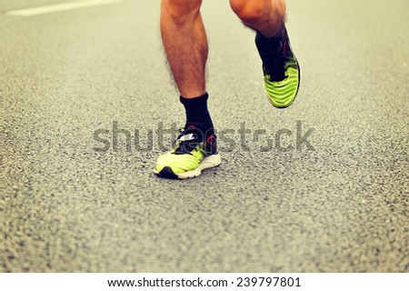 Unidentified marathon athlete legs running on city road