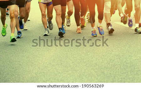 Unidentified marathon athletes competing in fitness and healthy active lifestyle feet on road - stock photo