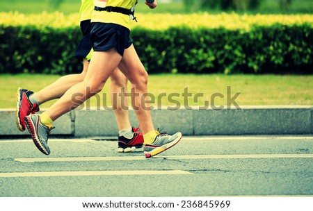 Unidentified marathon athletes legs running on city road  - stock photo