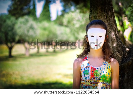 Unidentified masked young girl under the tree. Concept image about protection of children from violence, exploitation, abuse and neglect.