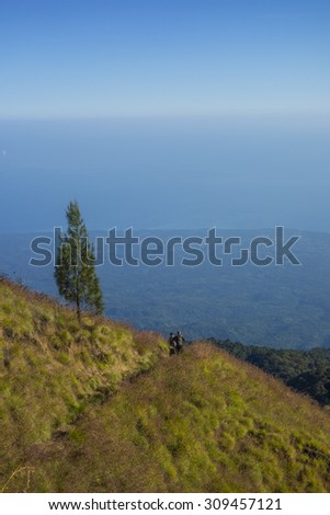 Unidentified mountain hikers or trekker walks slowly on trekking path on the way to Rinjani Mountain in Lombok, Indonesia. - stock photo