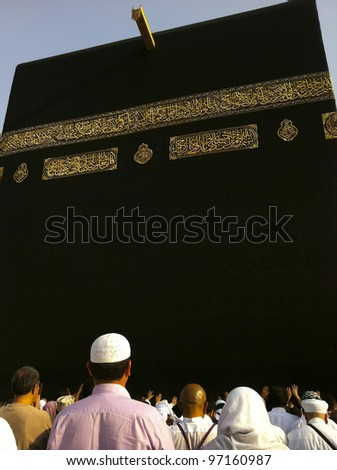 Unidentified Muslim pilgrims inside Hijr Ismail (Ishmael) compound close to the Kaabah. Muslims all around the world face the Kaaba during prayer time. - stock photo