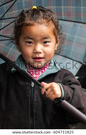 Unidentified Nepali girl holding umbrella close-up, Chame, Manang, Annapurna circuit, Himalaya, Nepal, September 20, 2012