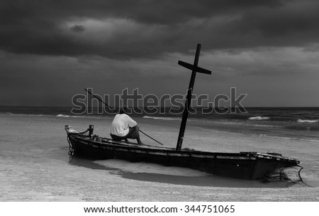 Unidentified old man on wreck boat on the beach with storm cloud in contrast Black and White - stock photo