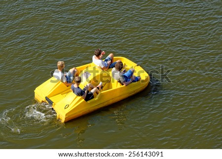 Unidentified people are enjoying a cruise on a pedal boat in Vltava river in Prague, Czech Republic. - stock photo