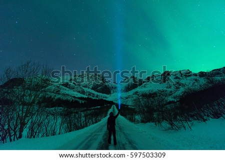 Unidentified Person Standing On A Road And Pointing Flashlight Beam To The Sky Filled With Aurora