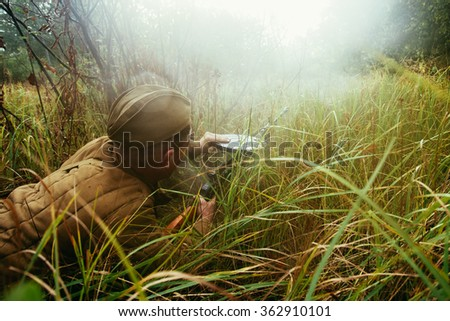 Unidentified re-enactor dressed as Soviet russian soldier reload machine gun in forest grass - stock photo