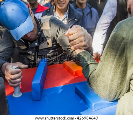 Unidentified sportsmen compete in arm wrestling against many people - stock photo