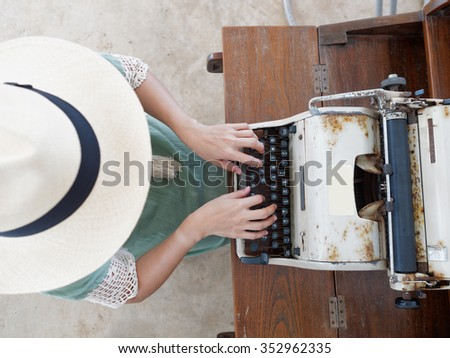 Unidentified woman's hand typing on retro typing machine  - stock photo