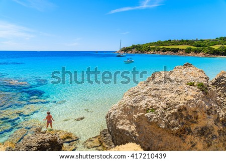 Unidentified woman standing in crystal clear turquoise sea water of Grande Sperone beach, Corsica island, France - stock photo