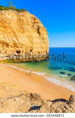 Unidentified woman walking on sandy beautiful Val Centianes beach, Algarve region, Portugal - stock photo