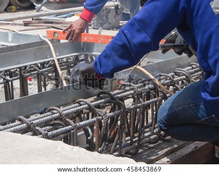 Unidentified worker is welding metal frame in construction site