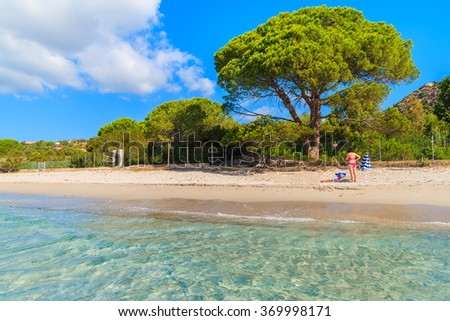 Unidentified young woman standing on beautiful Palombaggia beach, Corsica island, France - stock photo