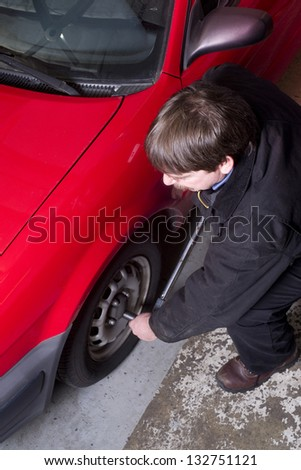 Uniformed Auto Technician Uses Breaker Bar Loosening Lug Nuts on Car - stock photo