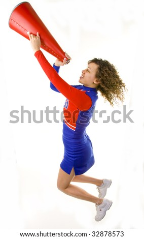 Uniformed cheerleader jumps high in  the air shouting through a megaphone,  isolated on white. - stock photo
