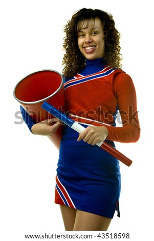 Uniformed cheerleader strikes a pose holding a spirit stick and a megaphone isolated on white.