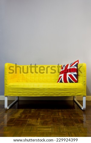 union jack backrest pillow on yellow modern fabric armchair / grey wall and wood floor , modern vintage style interior  - stock photo