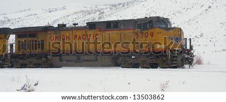 Union Pacific locomotive pulling freight train through snowstorm,			Colorado, Rocky Mountains